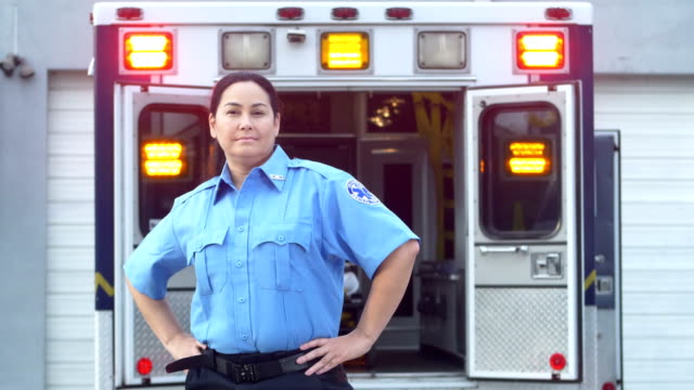 hispanic paramedic standing in front of ambulance - ambulance stock videos & royalty-free footage