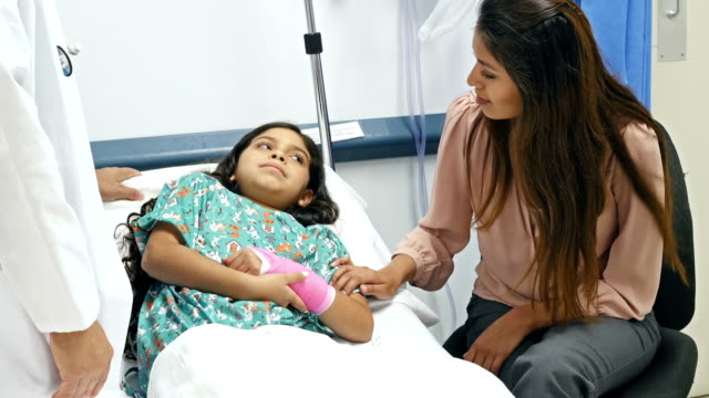 Hispanic pediatrician explaining procedure to patient and her mother