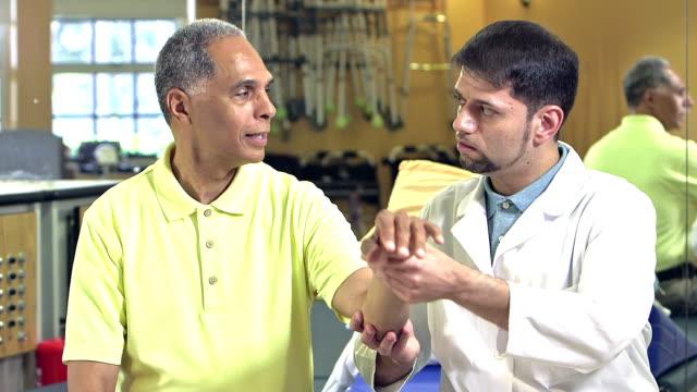 vídeos de stock, filmes e b-roll de hispânica fisioterapeuta examinando paciente - physical injury