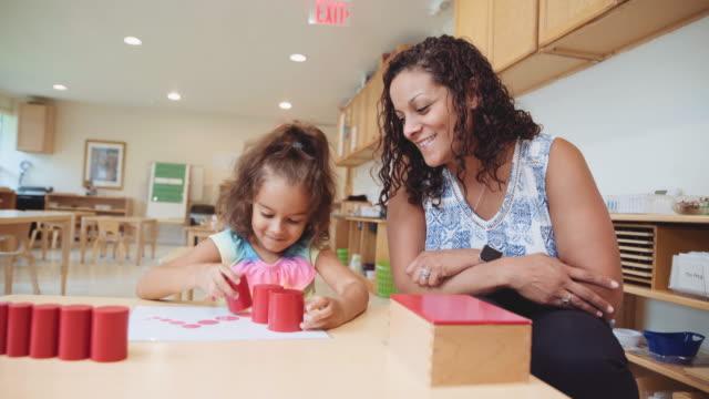 Hispanic preschool student and teacher