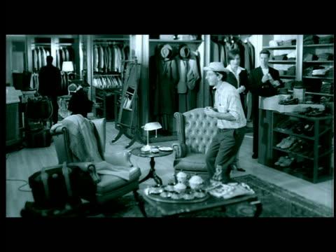 green letterbox hispanic saleswoman approaching man sitting in chair in men's clothing botique - ヒルビリー点の映像素材/bロール