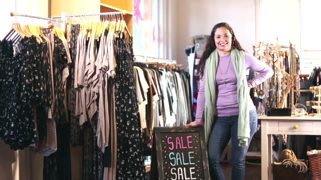 hispanic saleswoman in clothing store by sale sign - hand on hip stock videos & royalty-free footage