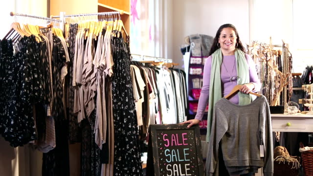 hispanic saleswoman in clothing store by sale sign - three quarter length stock videos & royalty-free footage