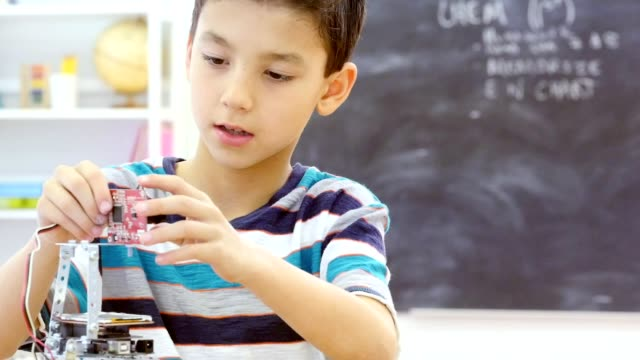 hispanic schoolboy concentrates while assembling robot - elementary school stock videos & royalty-free footage
