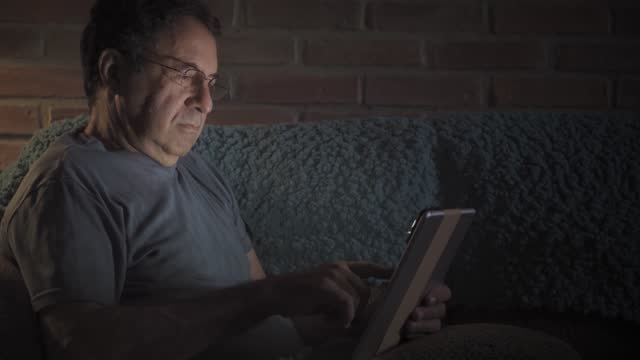 hispanic senior man using digital tablet on the sofa in the livingroom at home. leisure activities of active seniors during social distancing due to covid-19 pandemia - sofa stock videos & royalty-free footage