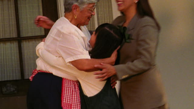 CANTED Hispanic senior woman being hugged by girl + woman on porch