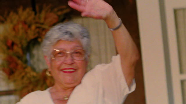 canted hispanic senior woman waving from porch - waving stock videos & royalty-free footage