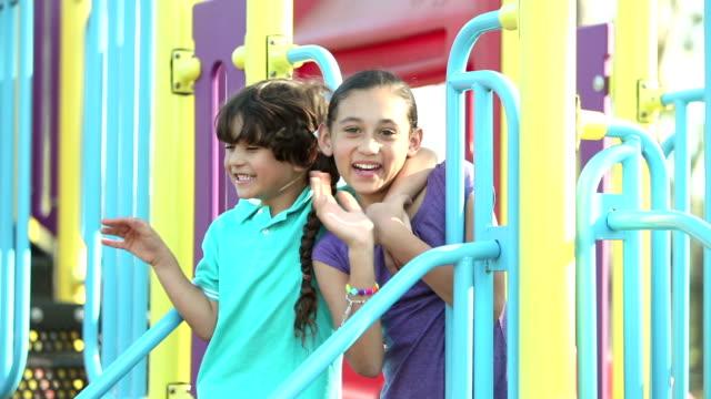 hispanische geschwister spielen auf spielplatz - geschwister stock-videos und b-roll-filmmaterial