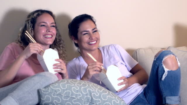 hispanic sisters watching tv, eating chinese takeout - take away food stock videos & royalty-free footage