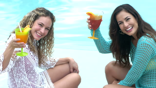 hispanic sisters with tropical drinks by swimming pool - tropical cocktail stock videos & royalty-free footage