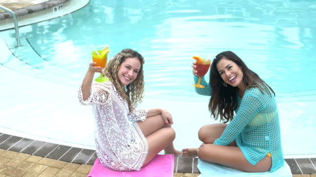 hispanic sisters with tropical drinks by swimming pool - tropical drink stock videos & royalty-free footage