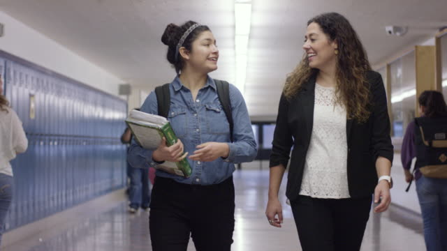 hispanic student walking the halls with her teacher - insegnante video stock e b–roll