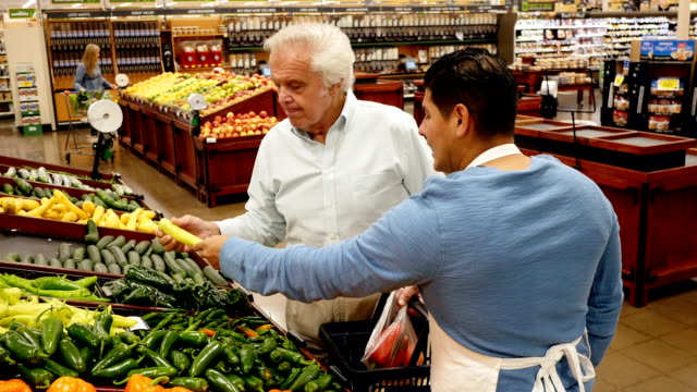Hispanic supermarket employee talks with senior Caucasian male customer about pepper varieties