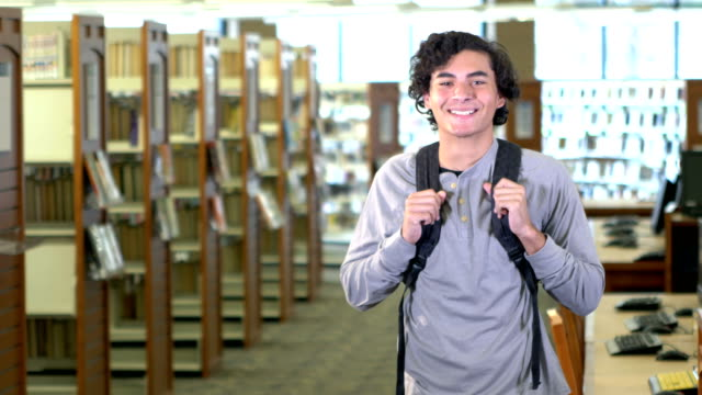 Hispanic teenage boy in high school library