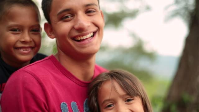 Hispanic teenage brother and younger siblings laugh at camera
