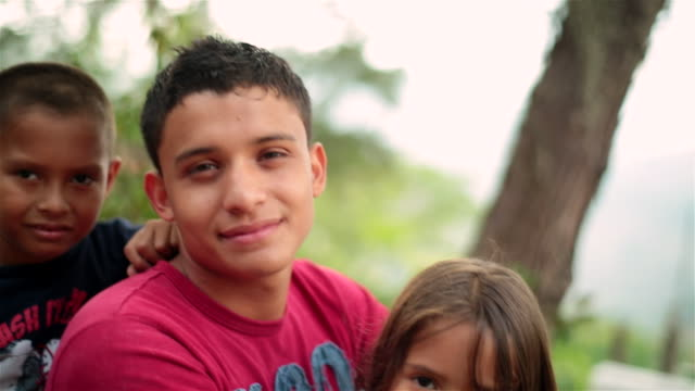 Hispanic teenage brother and younger siblings smile at camera, woman crosses in background