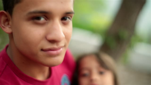 Hispanic teenage brother stares into camera, younger sister gazes at him admiringly