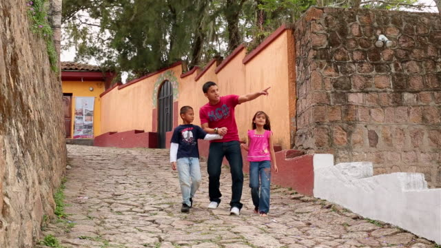 Hispanic teenage brother walks hand-in-hand, points out something to younger siblings