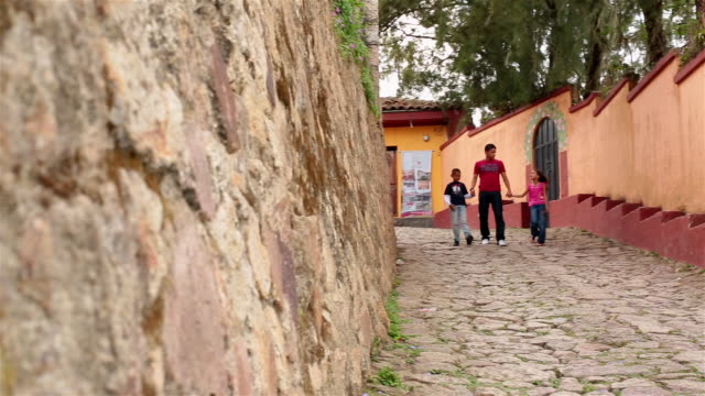 Hispanic teenage brother walks hand-in-hand with younger siblings down third-world street (dolly-shot)