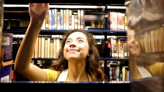 Spansktalande teenage hem skola gymnasiestudent finner boken i lokala offentliga bibliotek