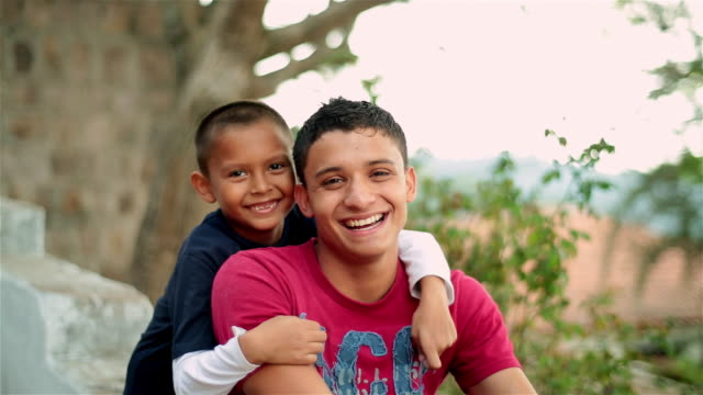 Hispanic teenager and younger brother smile and laugh at camera
