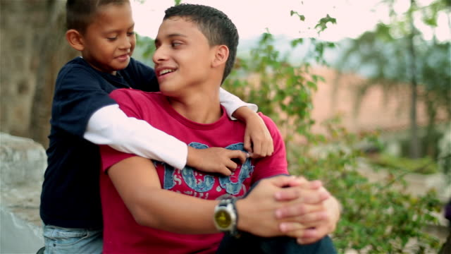 hispanic teenager talks and laughs with younger brother - brother stock videos & royalty-free footage