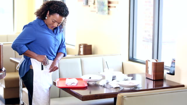 hispanic waitress clearing table in restaurant - gratuity stock videos & royalty-free footage