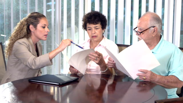 hispanic woman advising senior couple in home - brochure stock videos & royalty-free footage