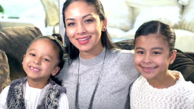 hispanic woman and two daughters sitting on couch - 6 7 years stock videos & royalty-free footage
