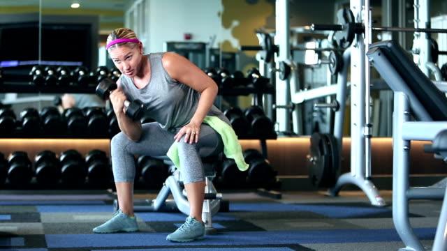 hispanische frau im fitnessstudio, heben hantel - bizeps stock-videos und b-roll-filmmaterial