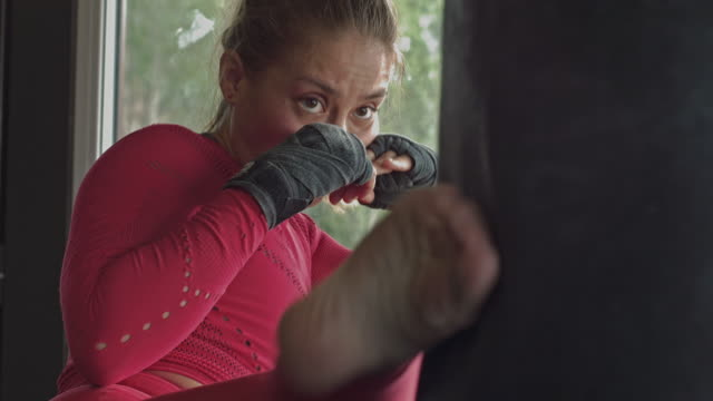 hispanic woman boxing a punching bag fighting fiercely - punch bag stock videos & royalty-free footage