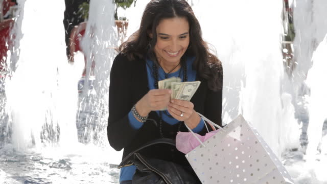 Hispanic woman counting money near fountain