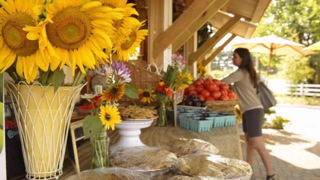 Hispanic woman examining produce at farm stand