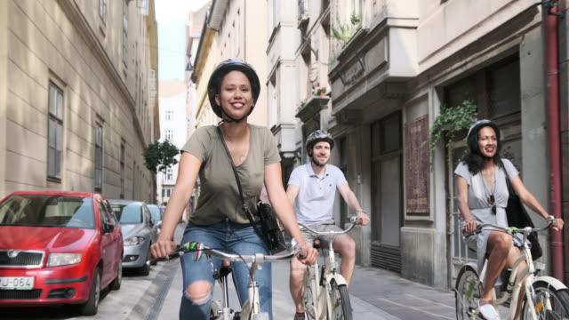 vidéos et rushes de femme hispanique explorant budapest sur des bicyclettes avec ses deux amis - vélo