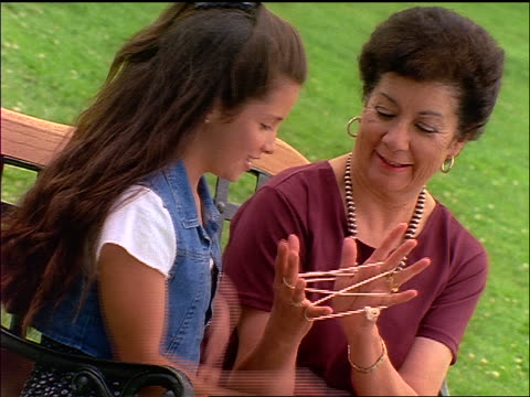 hispanic woman + girl sitting on bench playing cat's cradle outdoors - cat's cradle stock videos & royalty-free footage