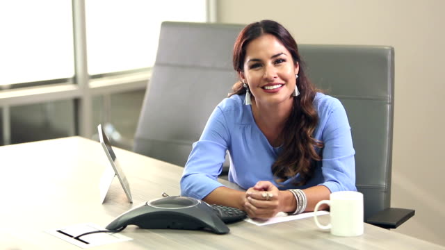 Hispanic woman in board room, smiling at camera
