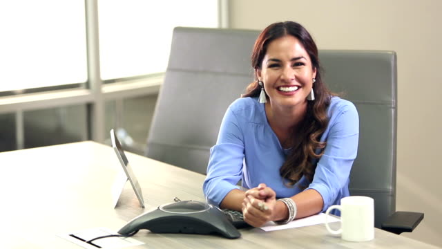 hispanic woman in board room, smiling at camera - conference phone stock videos & royalty-free footage