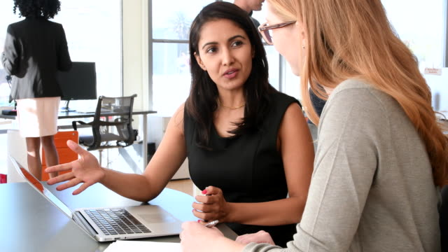 Hispanic woman in business discussion with colleague around laptop