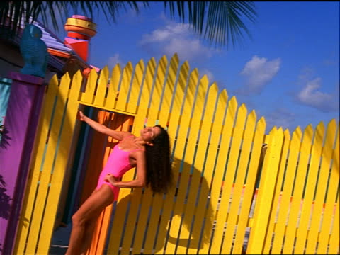 vídeos de stock, filmes e b-roll de canted hispanic woman in pink swimsuit standing by yellow fence posing / bahamas - maiô