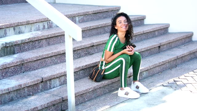 vidéos et rushes de la femme hispanique dans des vêtements d'entraînement attend à l'extérieur du bâtiment - vêtement de sport