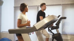 Hispanic woman is training on treadmill, talking and flirting with strong smiling man jogging near