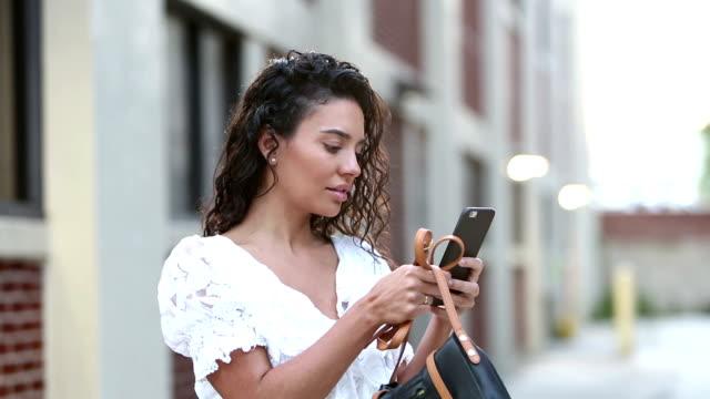 stockvideo's en b-roll-footage met hispanic vrouw kijkt naar mobiele telefoon op city street - 30 seconds or greater
