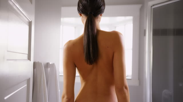 A Hispanic woman looks away from the camera seductively in her bathroom