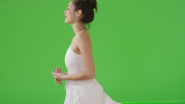 vidéos et rushes de a hispanic woman looks off on green screen - turning on or off