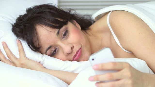 vídeos de stock, filmes e b-roll de hispanic woman lying in bed texting - só uma mulher de idade mediana