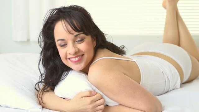 Hispanic woman lying in bed
