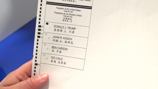hispanic woman manually filling out voter affidavit during the presidential primary elections / woman chooses presidential candidate donald trump /... - röstsedel bildbanksvideor och videomaterial från bakom kulisserna