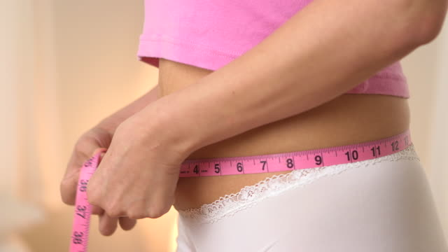 Hispanic woman measures waist size