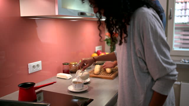 vidéos et rushes de femme hispanique versant du lait dans un café le matin - son