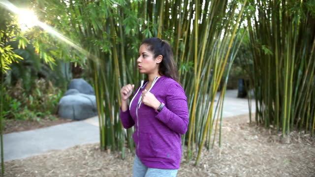 Hispanic woman power walking in park